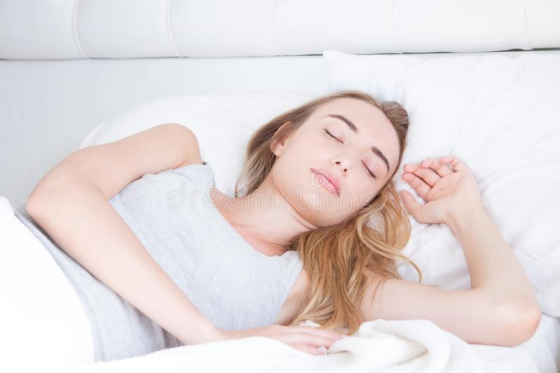 Sleep. Young Woman sleeping in bed, portrait of beautiful female resting on comfortable bed with pillows in white bedding in light stock photos