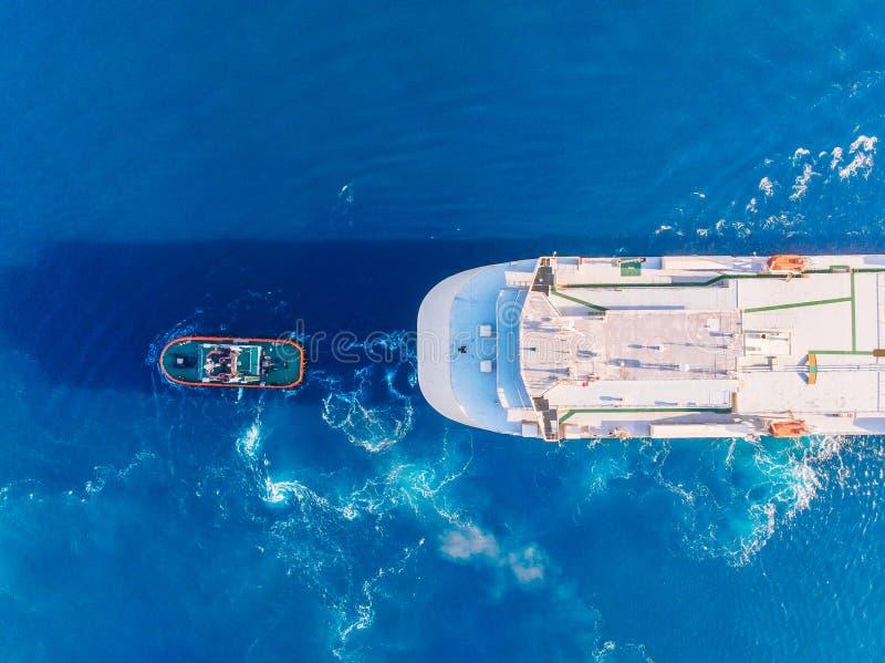 Sleepboot die de grote blauwe zeehaven van het containerschip slepen Lucht hoogste mening stock afbeelding