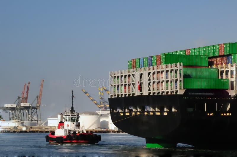 Sleepboot en rug van containerschip