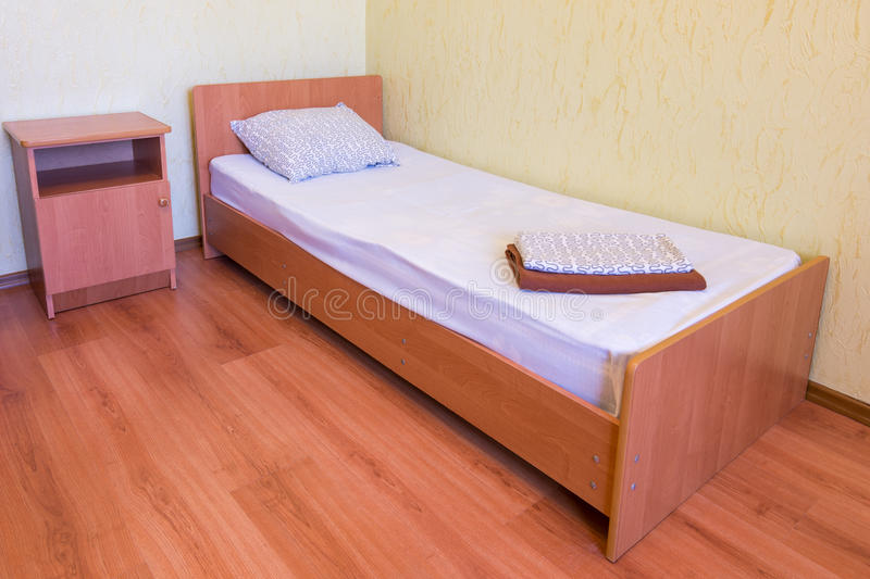 Sleeper - a bed and a bedside table in interior of the room, close-up royalty free stock photo