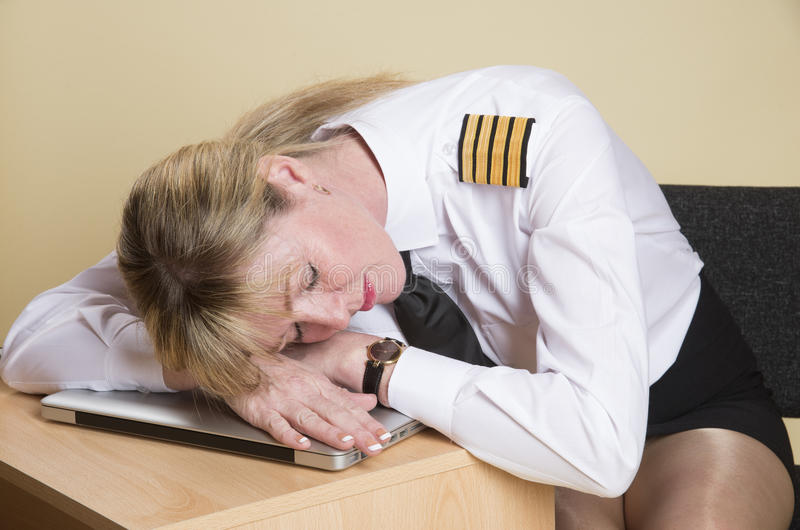 Sleeping airline pilot. Tired female airline pilot wearing insignia of a captain stock photo