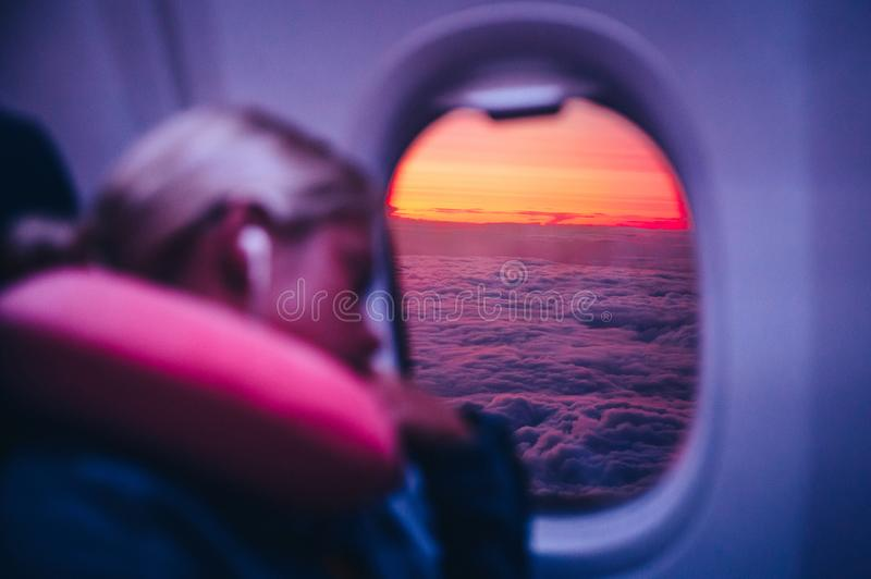 Sleeping in airplane, concept photo. Woman sleep in aircraft. Beautiful sunset sky and clouds behind the airplane window. Photo with natural light royalty free stock image