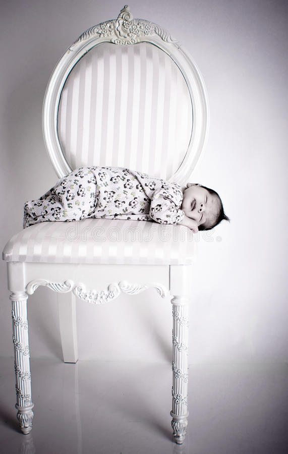 Sleeping baby. A 2 weeks old baby asleep on a white chair stock photography
