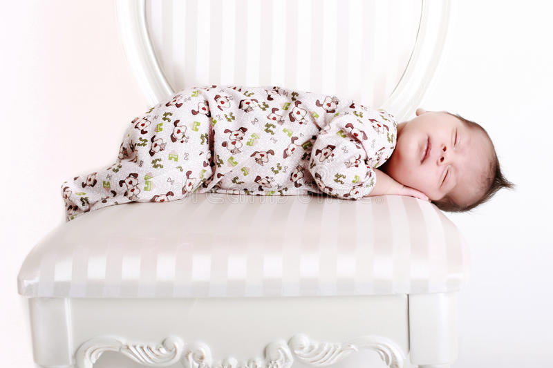 Sleeping baby. A 2 weeks old baby asleep on a white chair royalty free stock photography