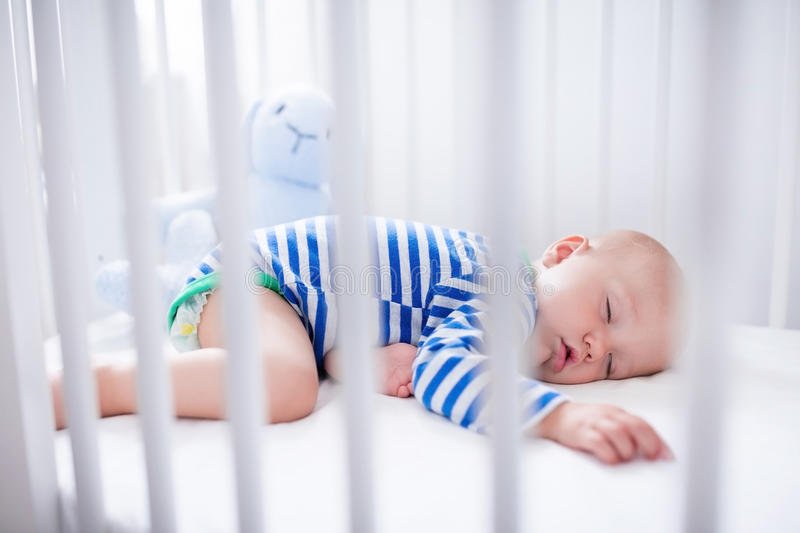 Sleeping baby boy in white crib. Sleeping baby and his toy in white crib. Nursery interior and bedding for kids. Cute little boy napping in bassinet. Kid taking stock image