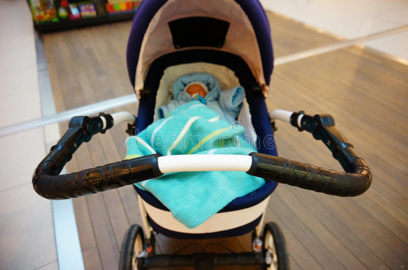Sleeping baby in buggy. Front part of an buggy with sleeping baby stock image
