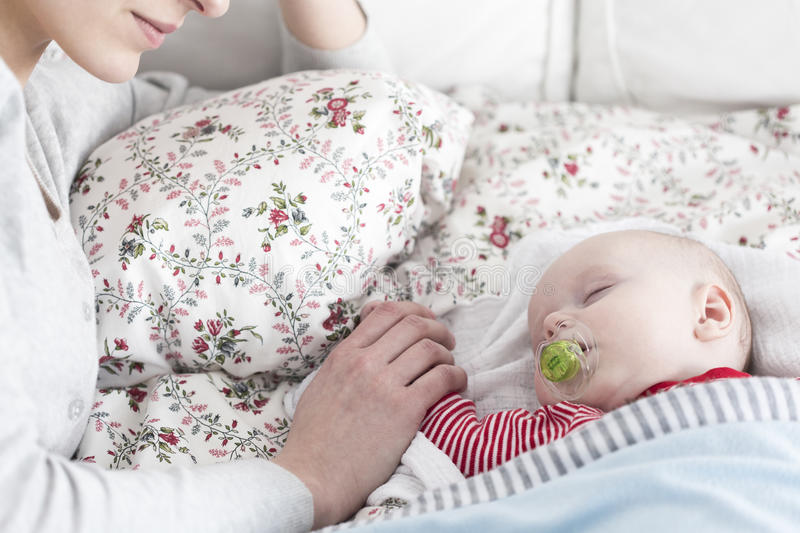 Sleeping baby and careful mother royalty free stock images
