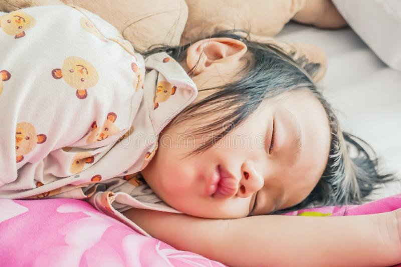 Sleeping baby or infant girl on bed in bedroom with teddy bear i royalty free stock photography
