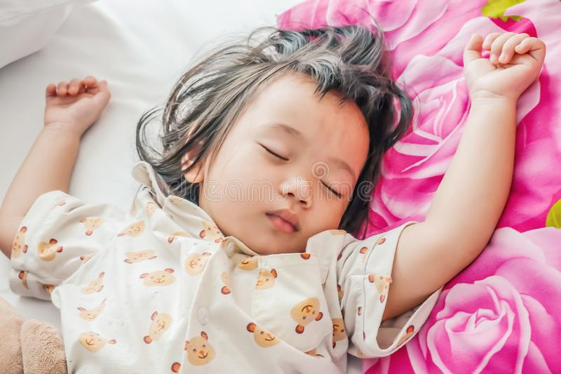 Sleeping baby or infant girl on bed in bedroom with teddy bear i stock image