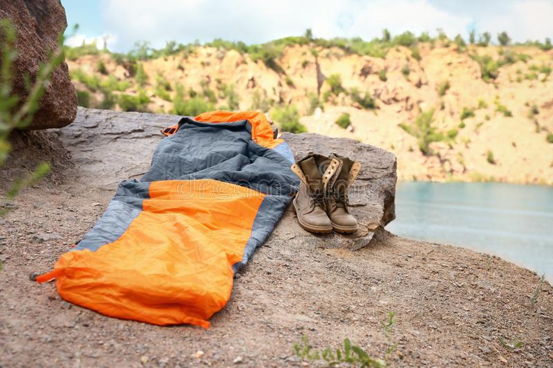 Sleeping bag and boots on cliff  lake. Space for text stock photos