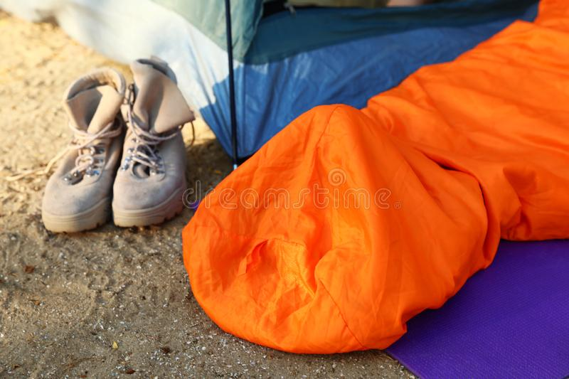 Sleeping bag and boots near tent royalty free stock photos