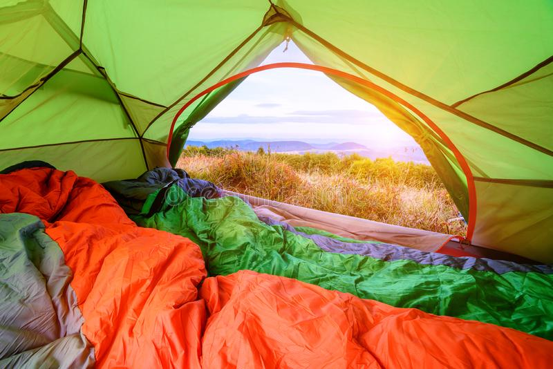 Sleeping bag inside a tent looking out with view through the back door royalty free stock photo