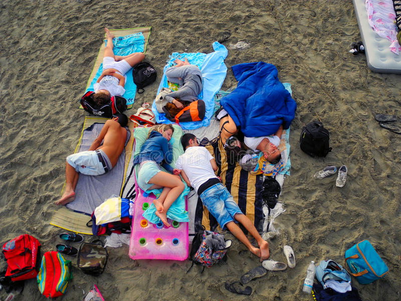 Sleeping on the beach. Spotorno, Italy - July 28 2013: Morning sleep of young people