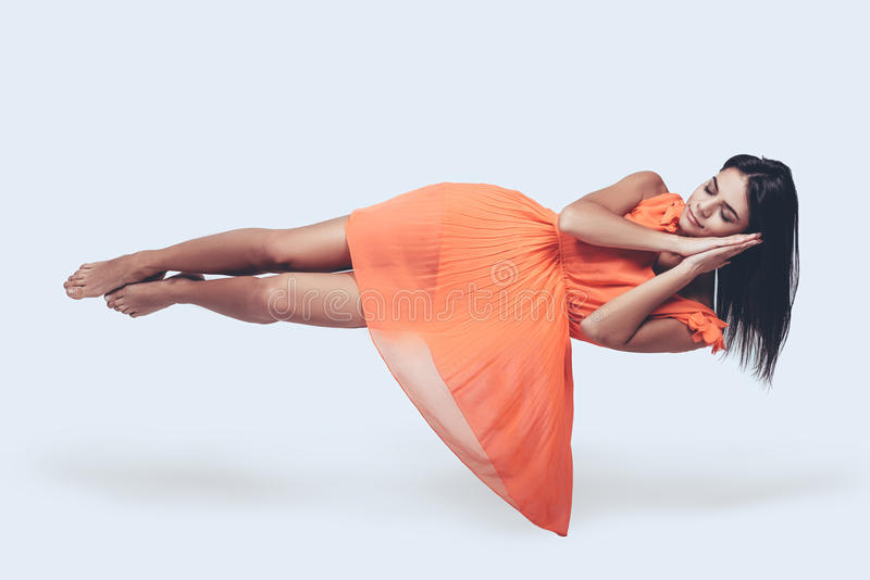 Sleeping beauty. Full length studio shot of attractive young woman in orange dress hovering in air and keeping eyes closed stock photography