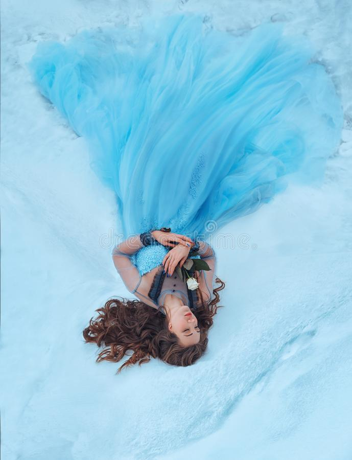 A sleeping beauty lies on the snow with a white rose in her hands. She is dressed in a luxurious, lush, blue dress stock image