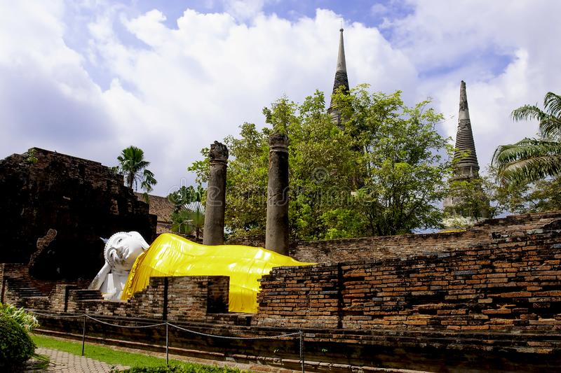 Sleeping Buddha Status at Wat Yai Chaimongkol, Ayutthaya, Thailand, with blue sky and white clouds behind.  stock photos