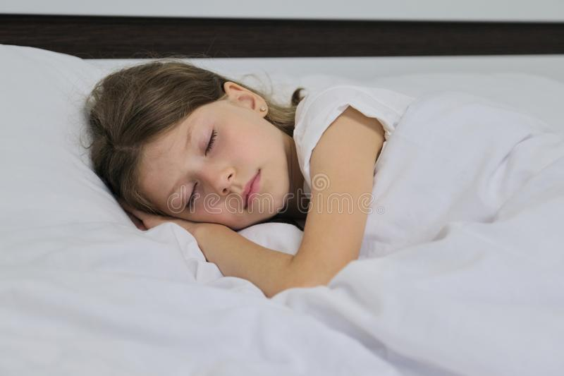 Sleeping child girl on a pillow, white bed, closeup face stock image