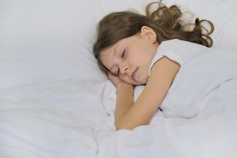 Sleeping child girl on a pillow, white bed, closeup face royalty free stock photo