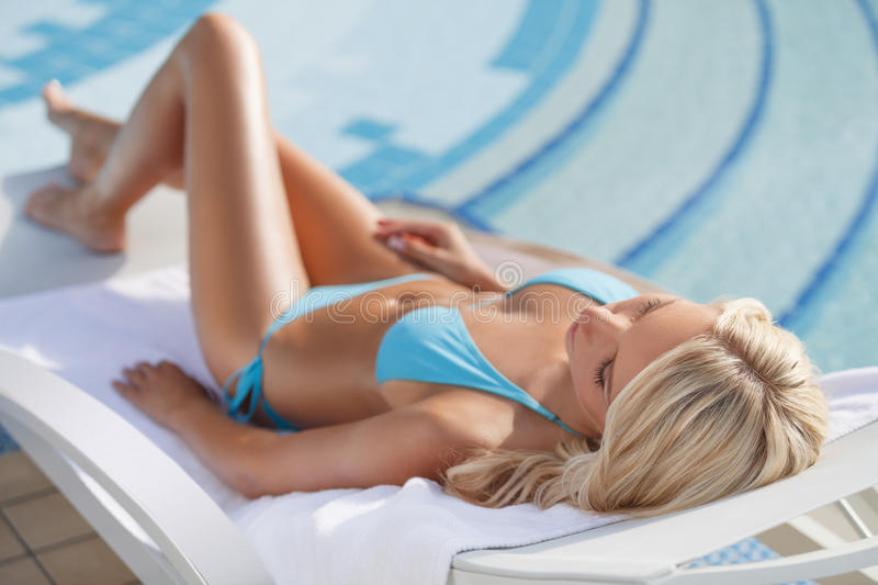 Sleeping on the deck chair. Beautiful young women in bikini sleeping on the deck chair near the pool royalty free stock photos