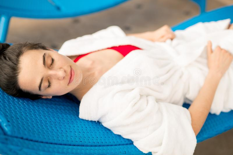 Sleeping on deckchair. Young brunette serene woman in white bathrobe lying on deckchair with her eyes closed at resort royalty free stock photo