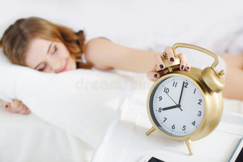 Sleeping girl with alarm stock photography