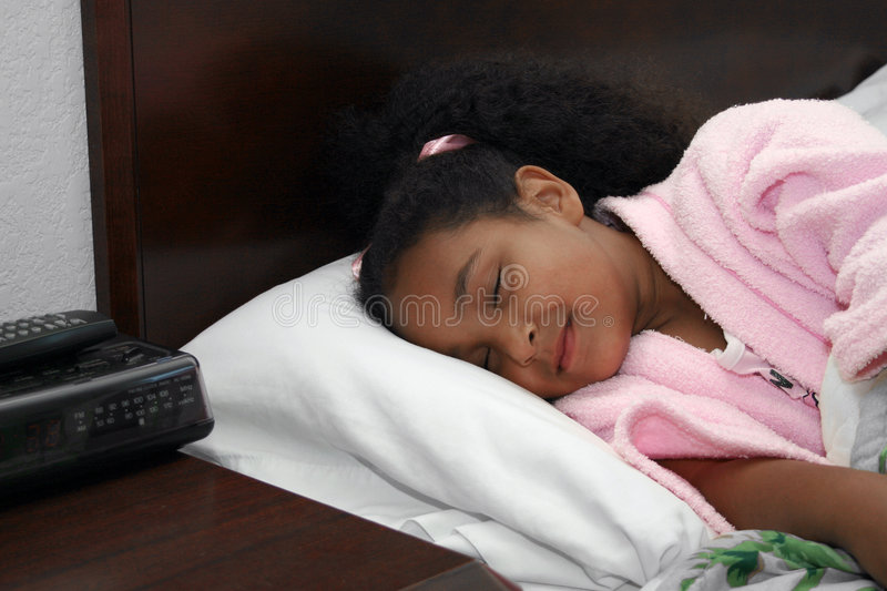 Sleeping girl in bed. Close up of cute smiling multiracial girl sleeping in bed stock image
