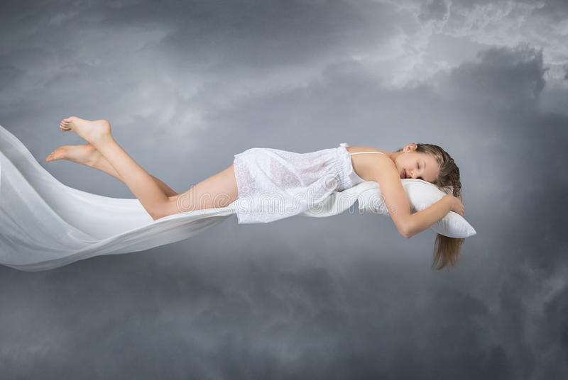 Sleeping girl. Flying in a dream. Clouds on grey background. royalty free stock photos