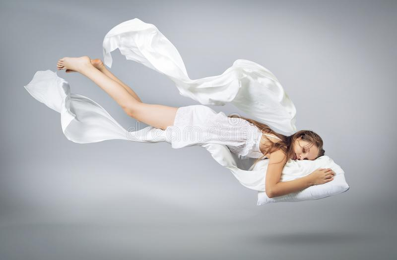Sleeping girl. Flying in a dream. White linen flying through the air. stock photography