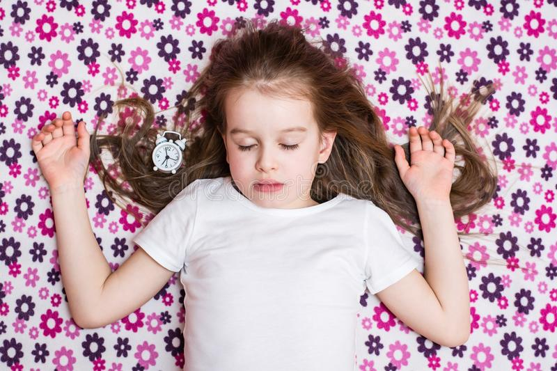 Sleeping girl and white alarm clock. Top view royalty free stock images