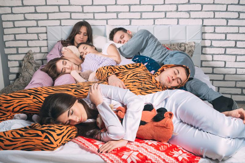 Sleeping Group Of Young People On The Bed. Stock Photo - Image of lying,  culture: 155365406