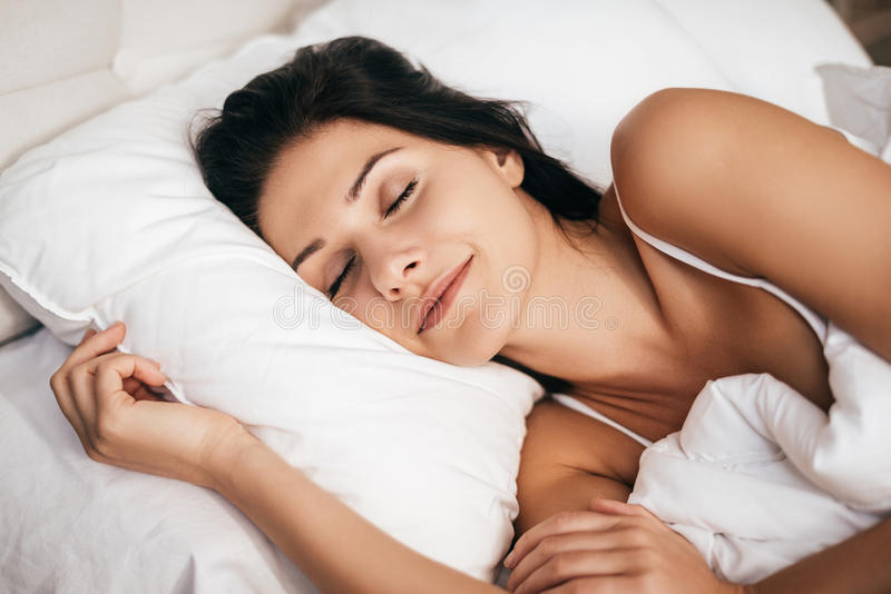 Sleeping at home. Beautiful young woman smiling during sleeping while lying in the bed at home stock photo