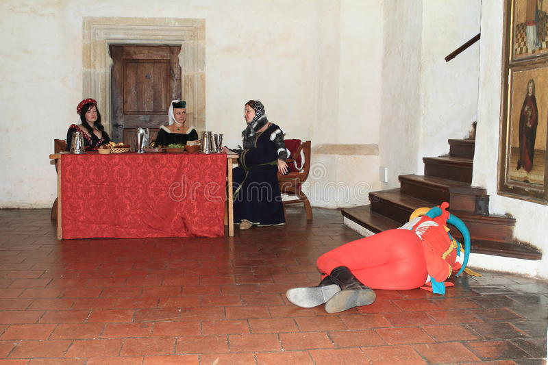 Sleeping jester. Jester in colorful costume sleeping on floor in banquet hall while noble women are eating and drinking during Night performance A dozen small stock photography