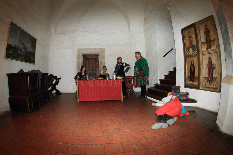 Sleeping jester. Jester in colorful costume sleeping on floor in banquet hall while noble women are eating and drinking and nobleman Puta talking during Night royalty free stock photography
