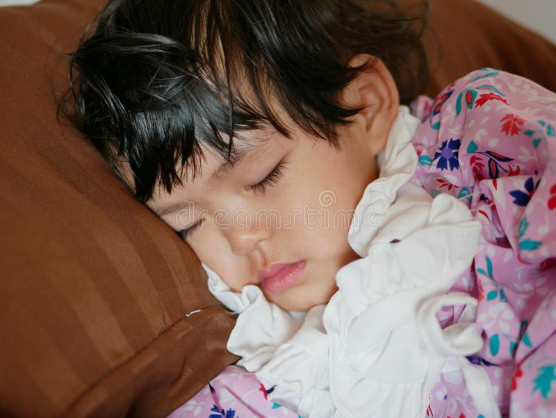 Sleeping little Asian baby girl on a pillow after a long day. Close up of sleeping little Asian baby girl, 24 months old, on a pillow after a long day royalty free stock photography
