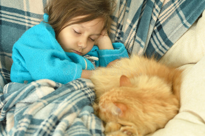 Sleeping little girl with red cat. Portrait of sleeping cute little girl with a red cat at home royalty free stock image