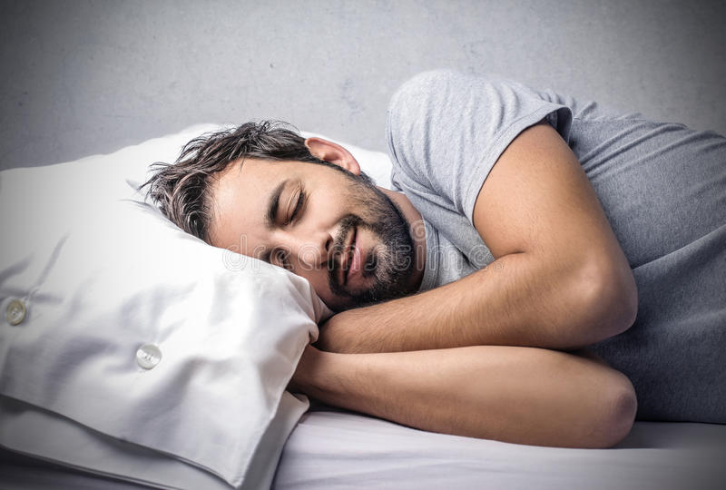 Sleeping man into bed stock images