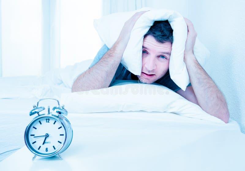 Sleeping man disturbed by alarm clock early mornin stock photo