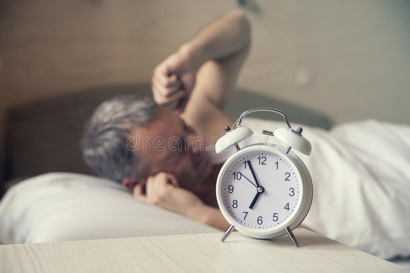 Sleeping man disturbed by alarm clock early morning. Angry man in bed awoken by a noise stock images