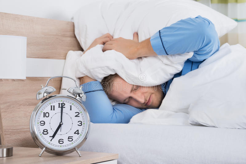Sleeping Man Disturbed By Ringing Alarm Clock stock image