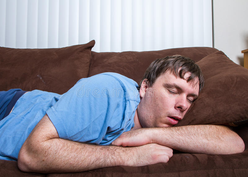 Sleeping man. Guy passed out on couch with arms wrapped around a pillow royalty free stock image