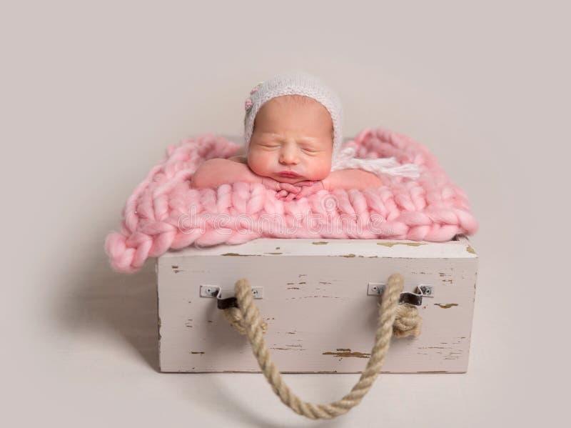 Sleeping newborn baby with chubby cheeks lying in box on rug royalty free stock image
