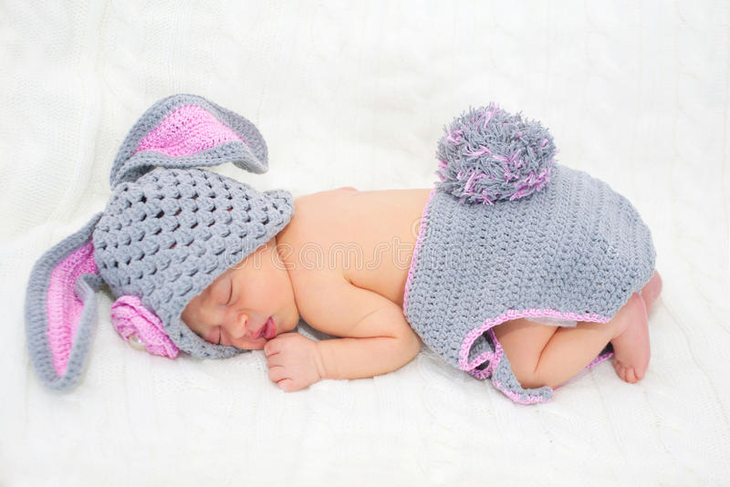 Sleeping newborn baby in Easter rabbit costume. On a knitted blanket royalty free stock photos