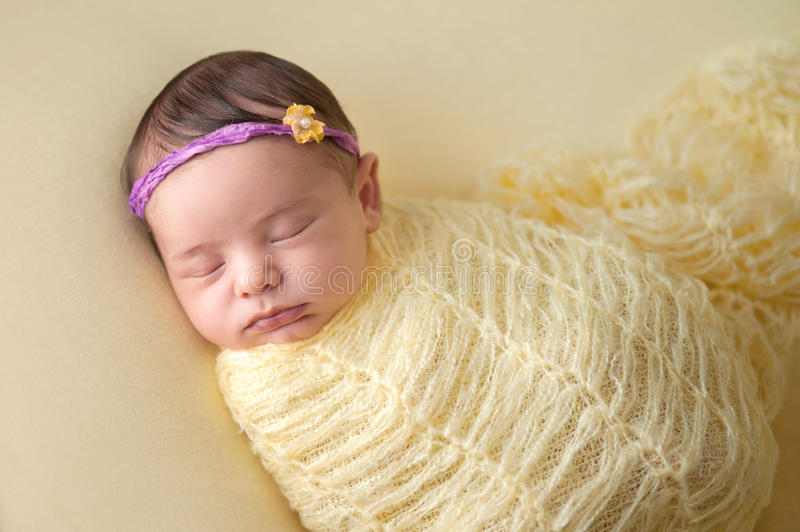 Sleeping Newborn Baby Girl Swaddled in Yellow royalty free stock photos