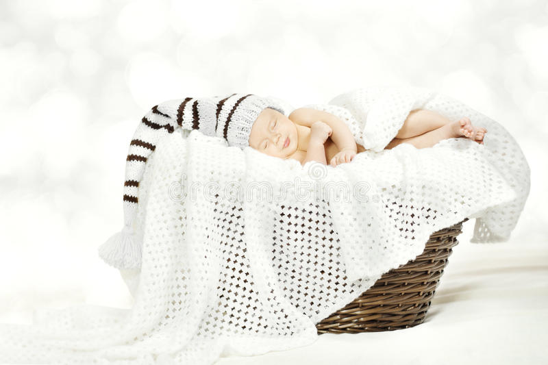 Sleeping newborn baby in hat lying in basket stock photos