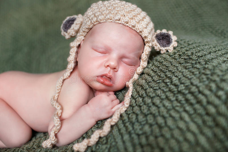 Sleeping newborn baby in a knitted blanket stock photos