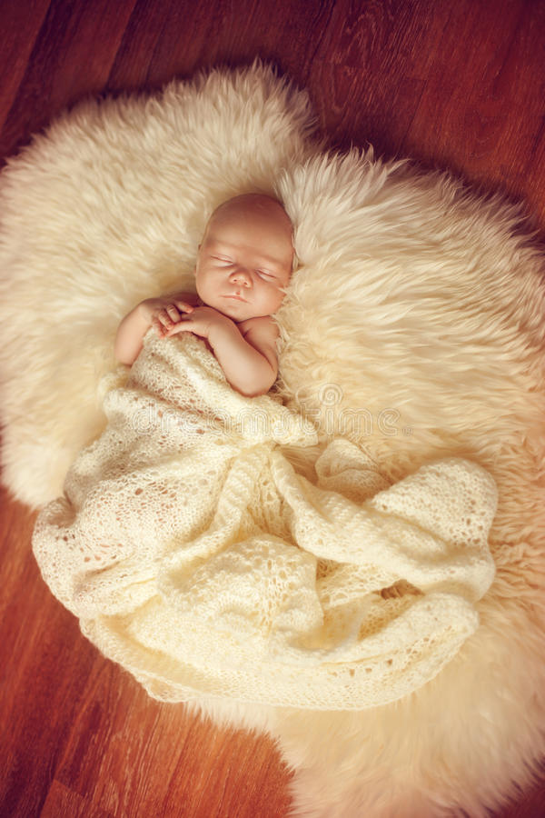 Sleeping newborn baby lying on white fur carpet covered with cream knitted blanket. royalty free stock image