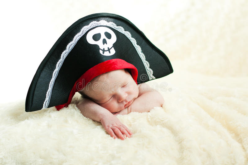 Sleeping newborn baby. In a pirate hat stock images