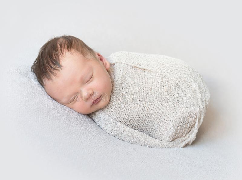 Lovely baby sleeping swaddled in a wrap, close-up. Sleeping newborn baby swaddled in a beige wrap on white blanket, close-up royalty free stock photography