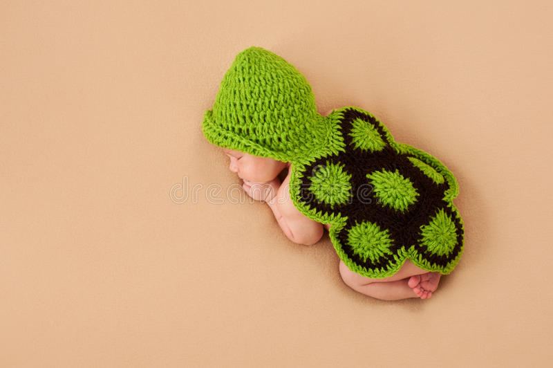 Sleeping Newborn Baby in Turtle Costume. A sleeping newborn baby wearing a crocheted turtle costume. Shot in the studio on a beige blanket royalty free stock photo