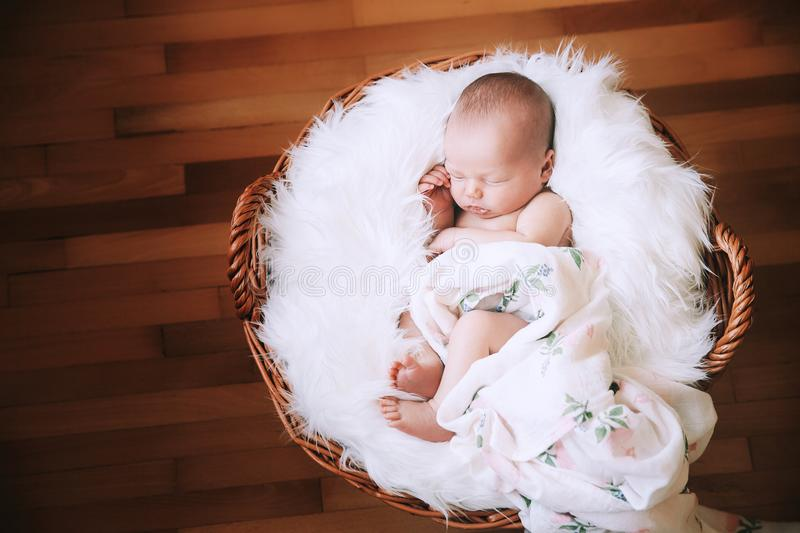 Sleeping newborn baby in a wrap on white blanket. royalty free stock photography